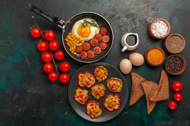 Widok z góry gotowana papryka z jajecznicą, chlebem i kiełbaskami na ciemnozielonej powierzchni