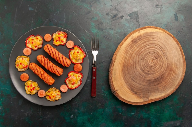 Widok z góry gotowana papryka z kiełbaskami i drewnianym biurkiem