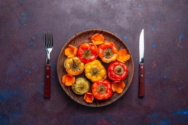 Widok z góry gotowana papryka z mielonym mięsem wewnątrz na szarym biurku posiłek jedzenie mięso gotowanie warzyw