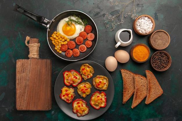 Widok z góry gotowane papryki z jajecznicą, bochenki chleba i kiełbaski na ciemnozielonej powierzchni
