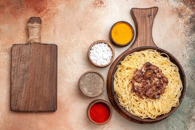 Widok z góry gotowane spaghetti z mielonym mięsem na jasnym stole z mięsem z ciasta makaronowego