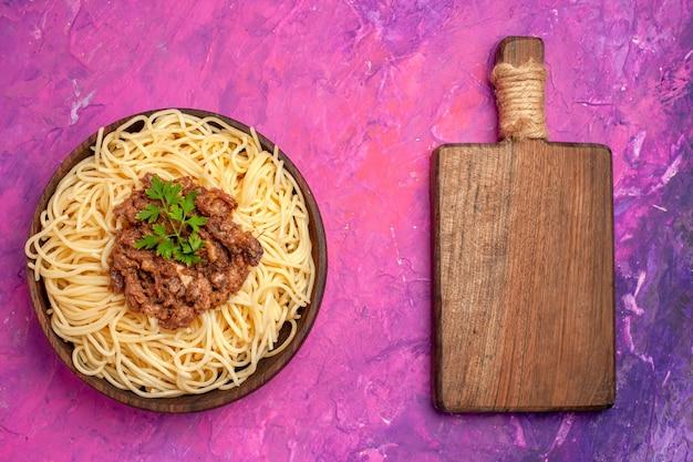 Widok z góry gotowane spaghetti z mielonym mięsem na różowej podłodze z ciasta makaronowego z mąką