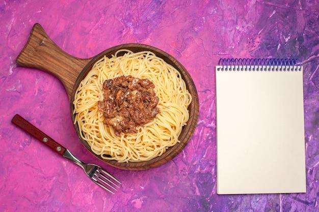 Widok z góry gotowane spaghetti z mielonym mięsem na różowym stole przyprawa do ciasta makaronowego