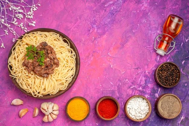 Widok z góry gotowane spaghetti z mielonym mięsem na różowym stole z przyprawą do ciasta makaronowego