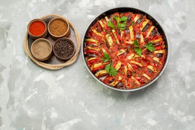 Widok z góry gotowane warzywa na okrągłej patelni wraz z przyprawami na jasnym tle posiłek warzywny danie obiad