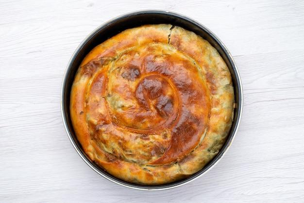 Widok z góry gotowane zielone ciasto okrągłe wewnątrz czarnej patelni na białym tle biurko posiłek jedzenie ciasto obiadowe zieleniny