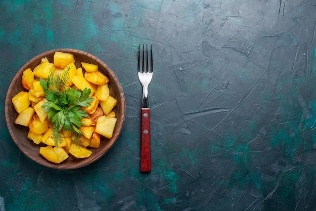 Widok z góry gotowane ziemniaki w plasterkach pyszny posiłek z zieleniną wewnątrz brązowego talerza na ciemnoniebieskim biurku