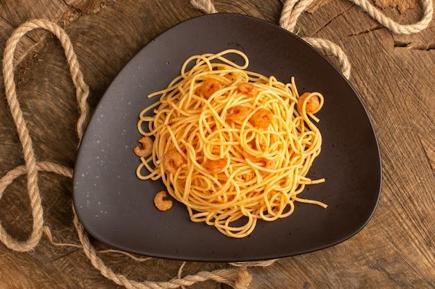 Widok z góry gotowanego włoskiego makaronu z krewetkami wewnątrz brązowego talerza z linami na drewnianym biurku