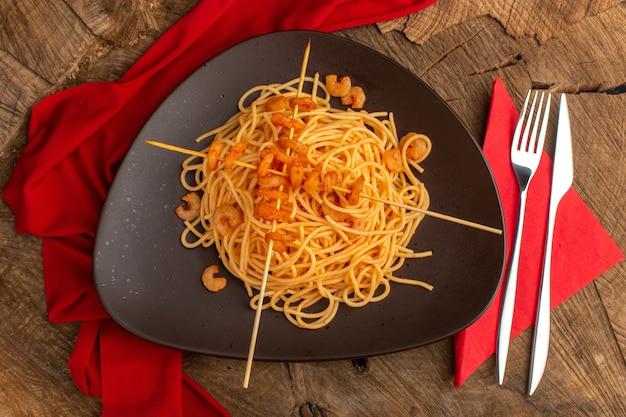 Widok z góry gotowanego włoskiego makaronu z krewetkami wewnątrz brązowego talerza ze sztućcami na drewnianej powierzchni