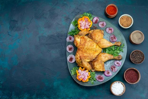 Widok z góry gotowany kurczak z cebulą i zieleniną wewnątrz talerza na granatowym biurku mięso kurczaka pieczone w piekarniku obiad