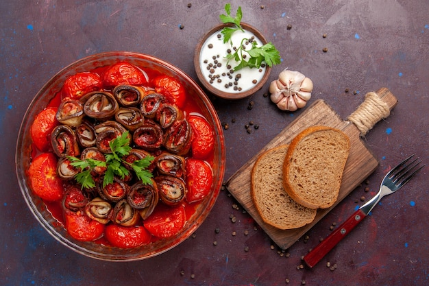 Widok z góry gotowany posiłek warzywny pyszne pomidory i bakłażany z bochenkami chleba i przyprawami na ciemnym biurku