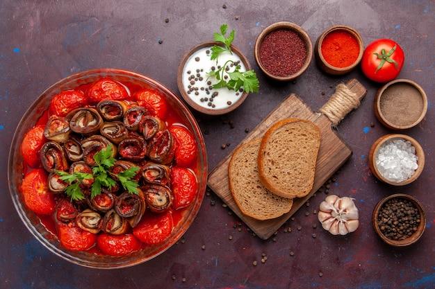 Widok z góry gotowany posiłek warzywny pyszne pomidory i bakłażany z przyprawami na ciemnej podłodze danie z warzywami