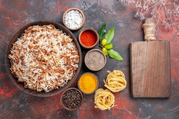 Widok z góry gotowany ryż z przyprawami na ciemnym danie z jedzeniem na biurko