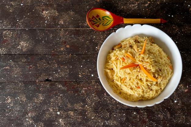 Widok z góry gotowany, solony i pieprzowy smaczny ryż wewnątrz okrągłego talerza na rustykalnym brązowym kolorze
