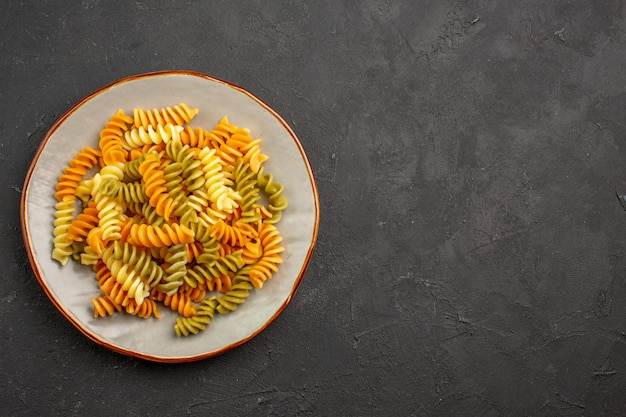 Widok z góry gotowany włoski makaron niezwykły spiralny makaron wewnątrz talerza na ciemnej przestrzeni