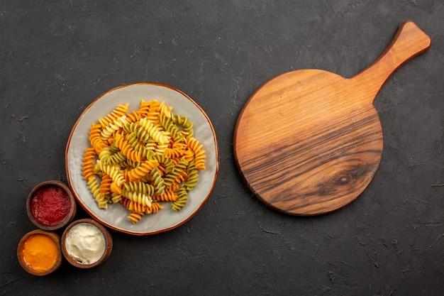 Widok z góry gotowany włoski makaron niezwykły spiralny makaron z przyprawami na ciemnej przestrzeni