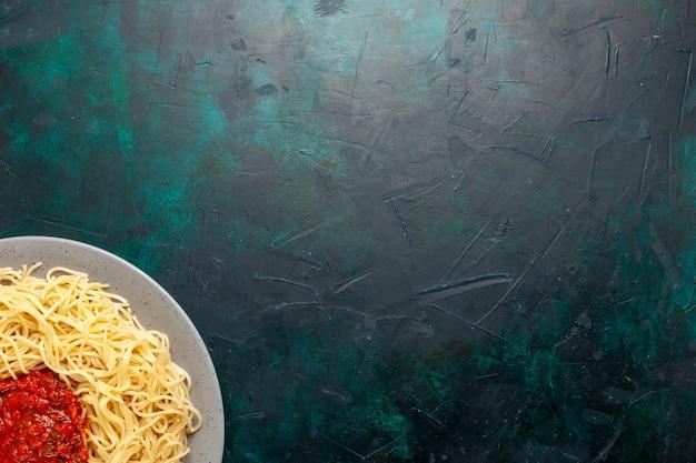 Widok z góry gotowany włoski makaron z mięsem mielonym i sosem pomidorowym na ciemnoniebieskiej powierzchni
