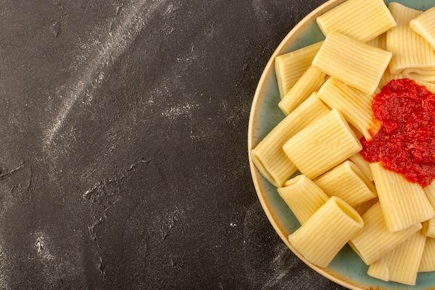 Widok z góry gotowany włoski makaron z sosem pomidorowym wewnątrz płyty