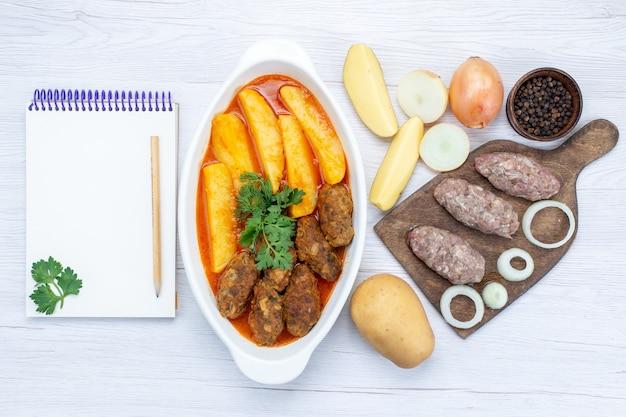 Widok z góry gotowanych kotletów mięsnych z sosem ziemniaczanym i zielonym wraz z surowym mięsem na lekkim biurku, jedzenie posiłek mięsny warzyw