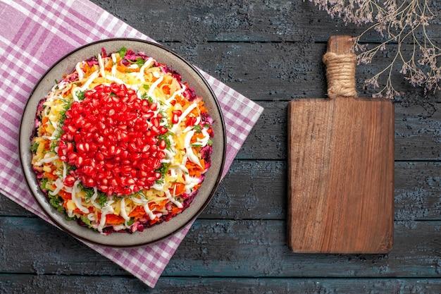 Widok z góry granat cytryna czosnek drewniana deska do krojenia obok gałęzi drzew i talerz z apetycznym daniem na obrusie w różowo-białą kratkę na stole