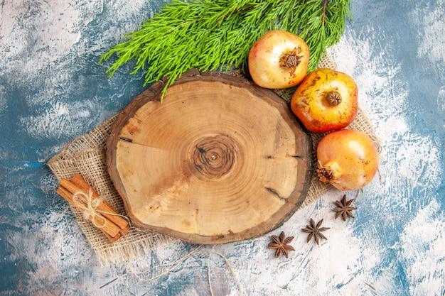 Widok z góry granaty drzewo deska drewniana cynamon nasiona anyżu na niebiesko-białym tle