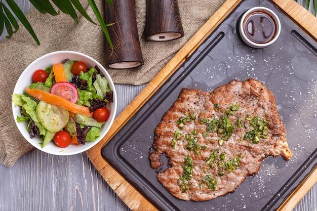 Widok z góry grillowane kotlety mięsne z surówką i sosem na tablicy