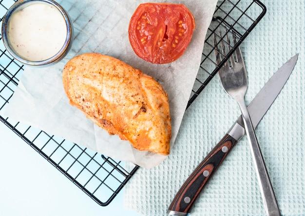 Widok z góry grillowany kurczak z pomidorami i sosem
