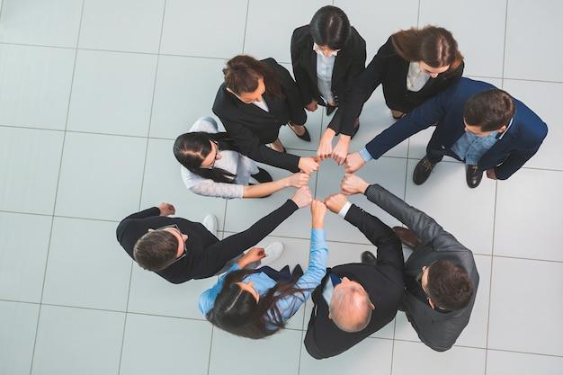 Widok z góry. grupa młodych profesjonalistów stojących w kręgu. pojęcie pracy zespołowej