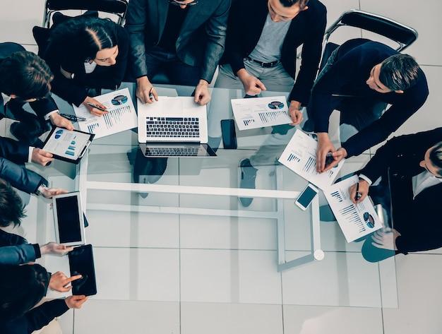 Widok z góry. grupa robocza omawiająca biznesplan finansowy. zdjęcie z miejscem na kopię.