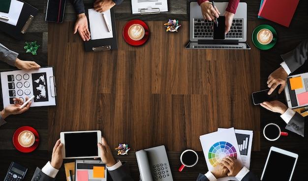 Widok z góry grupy biznesowej wieloetnicznych ludzi zajęty spotkanie z innymi w nowoczesnym biurze z laptopa, smartfona, tabletu, kawy i dokumentu na stole.