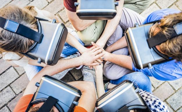 Widok z góry grupy przyjaciół gry na okulary vr z układaniem rąk