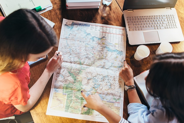 Widok z góry grupy studentek studiujących mapę siedzi przy biurku