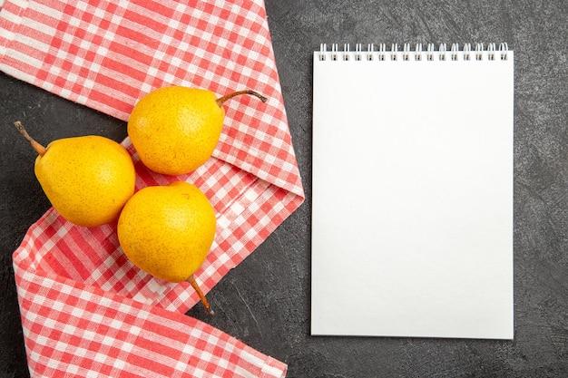 Widok z góry gruszki na obrusie biały notes obok gruszek na obrusie w kratkę na czarnym stole