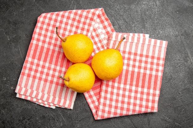 Widok z góry gruszki na obrusie trzy gruszki na obrusie w różowo-białą kratkę na ciemnym stole