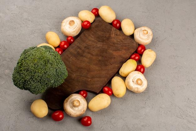 Widok z góry grzyby brokuły ziemniaki wraz z czerwonymi pomidorami cherry na szarym biurku
