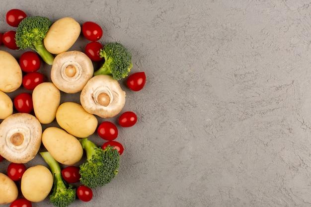 Widok z góry grzyby wraz z czerwonymi pomidorami cherry i świeżymi dojrzałymi brokułami na jasnej podłodze