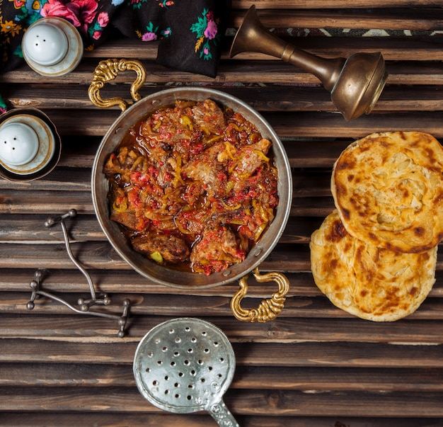 Widok z góry gulasz wołowy, govurma w sosie pomidorowym z ziołami i chlebem tandir.
