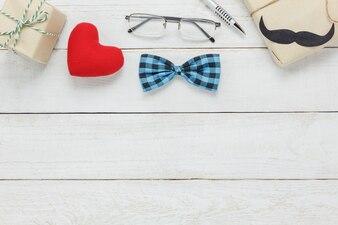 Widok z góry Happy Father day.accessories z czerwonym sercem, wąsy, zabytkowe dziobu krawat, obecne, długopis na rustykalnym białym tle drewniane.