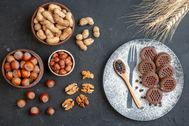 Widok z góry herbatniki kakaowe drewniana łyżka na talerzu z widelcem nadruk z cukrem pudrem orzechy w miseczkach nasiona dyni orzechy włoskie orzeszki ziemne orzechy laskowe kolce pszenicy na ciemnym tle