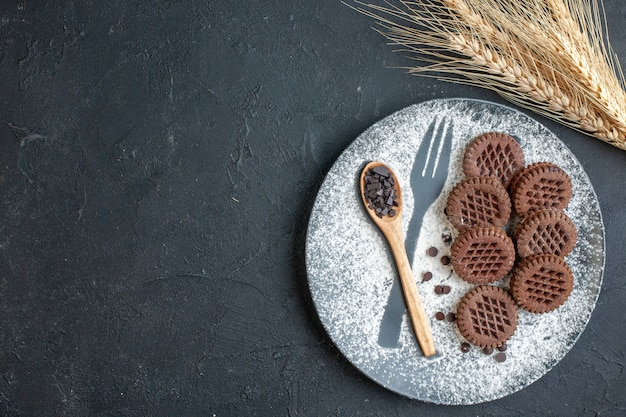 Widok z góry herbatniki kakaowe drewniana łyżka na talerzu z widelcem odcisk z pudrem kolce pszenicy na ciemnym tle miejsce kopiowania