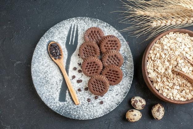 Widok z góry herbatniki kakaowe drewniana łyżka na talerzu z widelcem odcisk z pudrem płatki owsiane w misce kolce pszenne jajka przepiórcze na ciemnym tle