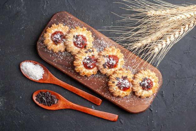 Widok z góry herbatniki z dżemem na drewnianej desce proszek kokosowy i proszek czekoladowy w drewnianych łyżkach kłosy pszenicy na ciemnym tle