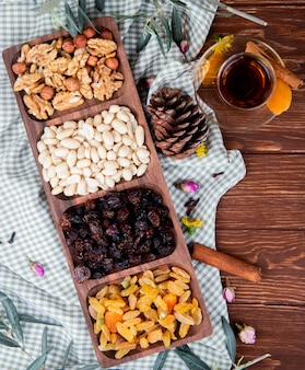 Widok z góry herbaty w szklance armudu z mieszanymi orzechami i suszonymi owocami w drewnianym pudełku na drewnie