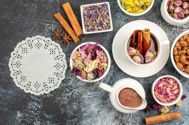 Widok z góry herbaty ziołowej z roztopioną czekoladą i suszonymi kwiatami oraz kawałkiem koronki na szarym podłożu