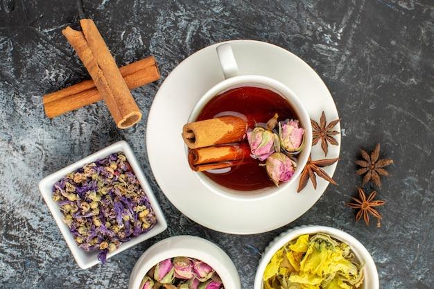 Widok z góry herbaty ziołowej z suchymi kwiatami na szaro