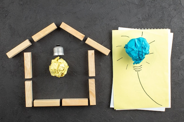 Widok z góry idealna żarówka w drewnie w kształcie domu blokuje idealną żarówkę na notatniku na czarno
