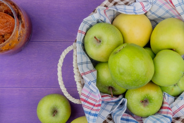 Widok z góry jabłek w koszu z dżemem jabłkowym na fioletowym tle