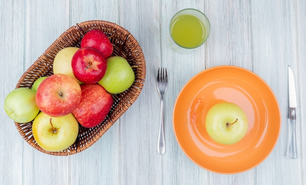 Widok z góry jabłek w koszyku i zielony w płycie z nożem do soku jabłkowego i widelcem na drewnianym stole