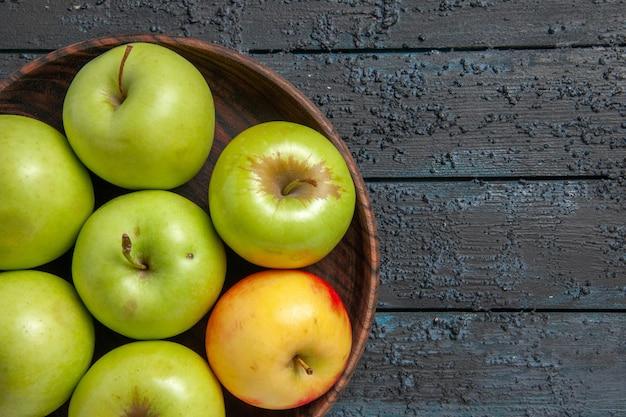 Widok z góry jabłka na stole siedem zielono-żółto-czerwonych jabłek w misce po lewej stronie ciemnego stołu