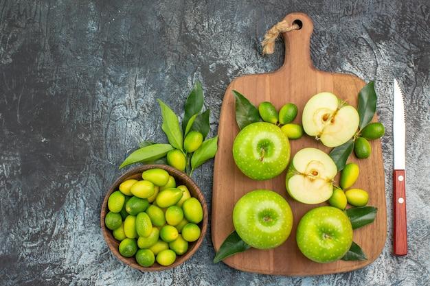 Widok z góry jabłka z bliska drewniana deska z jabłkami z liśćmi nóż miska owoców cytrusowych
